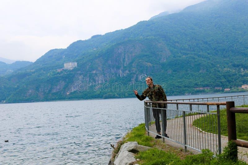 Kaukasischer Tourist in der Nähe von Banister, See Como und Alpen Berg im Hintergrund stockbilder