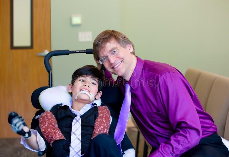 Kaukasischer Vater im purpurroten dresshirt und Krawatte, die nahe bei sitzt stockfotografie