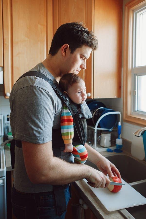 Kaukasischer Vater mit neugeborenem Baby in der Fördermaschine, die das Mittagessen vorbereitet lizenzfreies stockbild