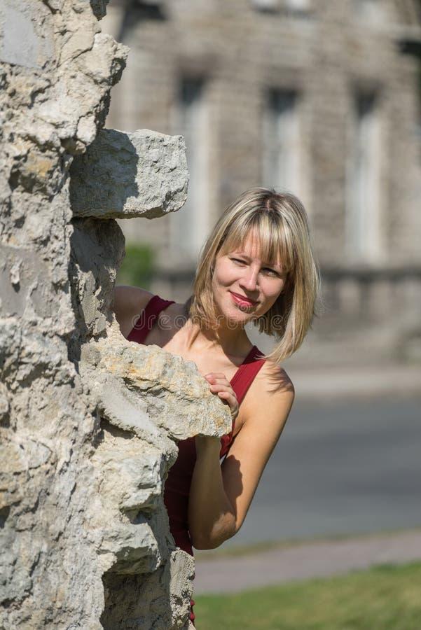 Kaukasischer weißer weiblicher Modell- und Ziegelsteinstein Frau in einem roten Kleid, das hinter der Wand im Stadtpark steht stockfotos