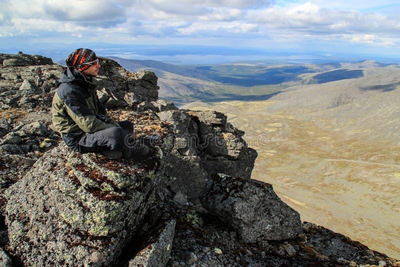 Kaukasischer weißer männlicher Tourist in der Sportkleidung, im Büffelleder und in den Gläsern sitzt auf einem Felsen stockfotos