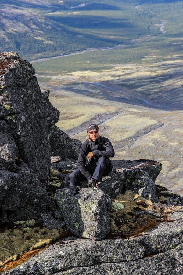 Kaukasischer weißer männlicher Tourist in der Sportkleidung, im Büffelleder und in den Gläsern sitzt auf einem Felsen lizenzfreies stockbild