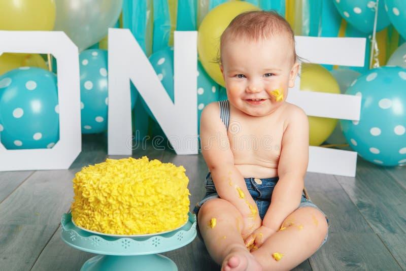 Kaukasisches Baby, das seinen ersten Geburtstag feiert Kuchenzertrümmern lizenzfreie stockbilder