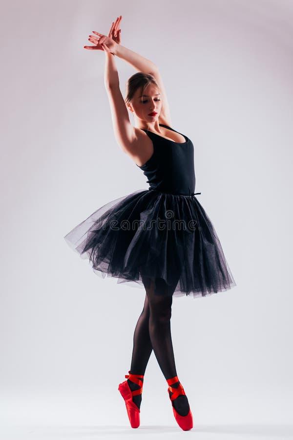 Kaukasisches Ballerina-Balletttänzertanzen der jungen Frau mit Ballettröckchen im Schattenbild stockfotografie