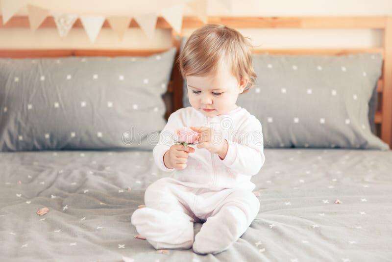 Kaukasisches blondes Baby im weißen onesie, das auf Bett im Schlafzimmer sitzt lizenzfreie stockbilder