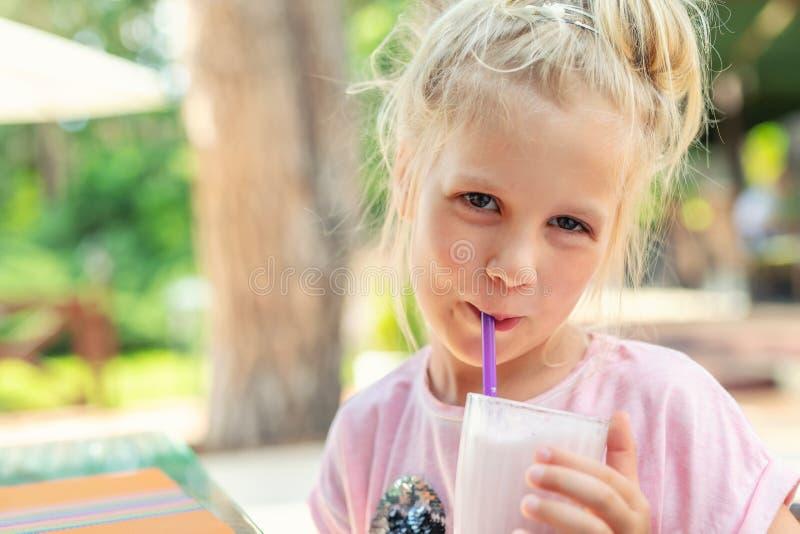 Kaukasisches blondes Mädchenporträt des entzückenden netten Vorschülers, das draußen an neuem geschmackvollem Erdbeermilchshake c stockbilder