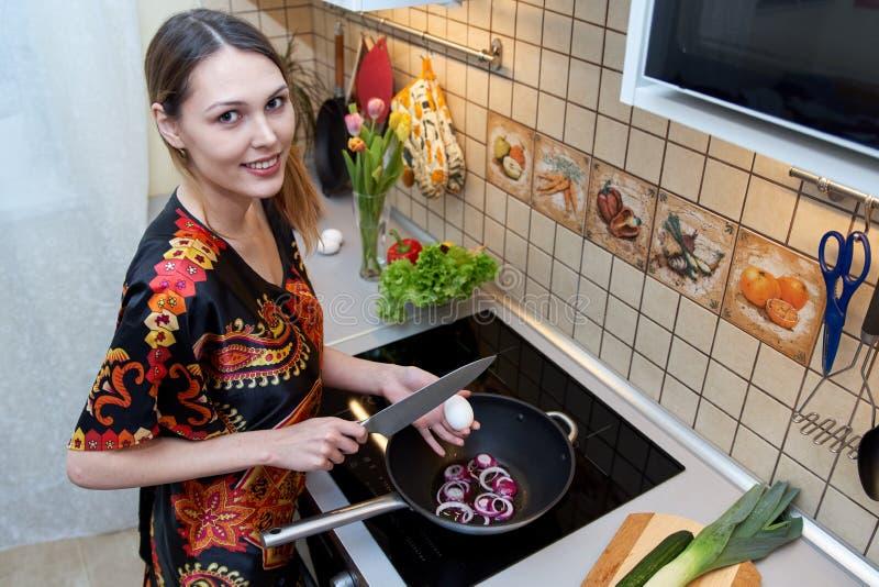 Kaukasisches hübsches Mädchen mit einem Lächeln tut das Kochen im kitch lizenzfreies stockfoto