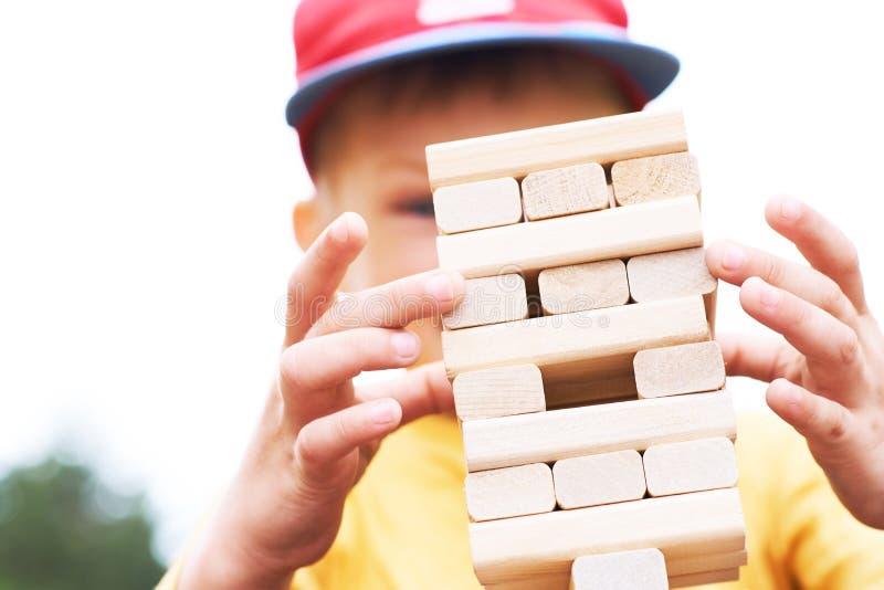 Kaukasisches Kind spielt Turmspiel der hölzernen Blöcke für das Üben der körperlichen und Geistesfähigkeit stockfotos