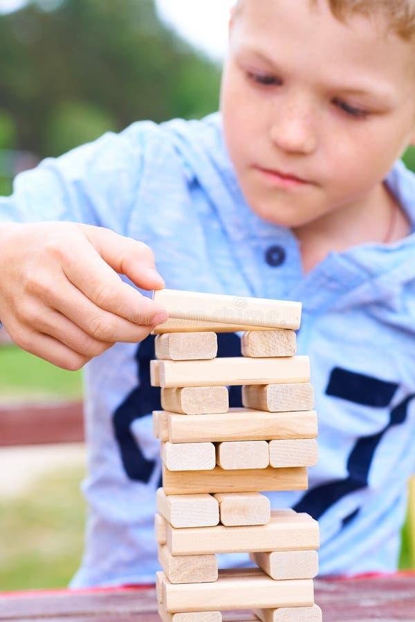 Kaukasisches Kind spielt Turmspiel der hölzernen Blöcke für das Üben der körperlichen und Geistesfähigkeit lizenzfreie stockfotografie