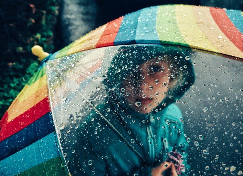 Kaukasisches Mädchen, das durch Regenbogenregenschirm mit großen Regentropfen schaut lizenzfreie stockfotos