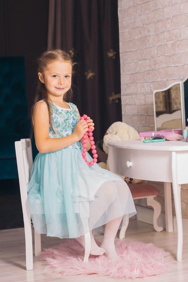 Kaukasisches Mädchen in einem blauen Kleid sitzt auf einem Stuhl am Frisiertisch und hält rosa Perlen in den Händen lizenzfreies stockfoto