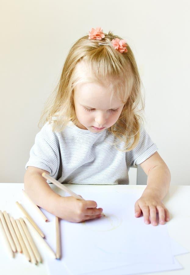 Kaukasisches Mädchen, welches zu Hause die bunte Bleistift-Früherziehung sich vorbereitet für Schulvorschule malt stockbild