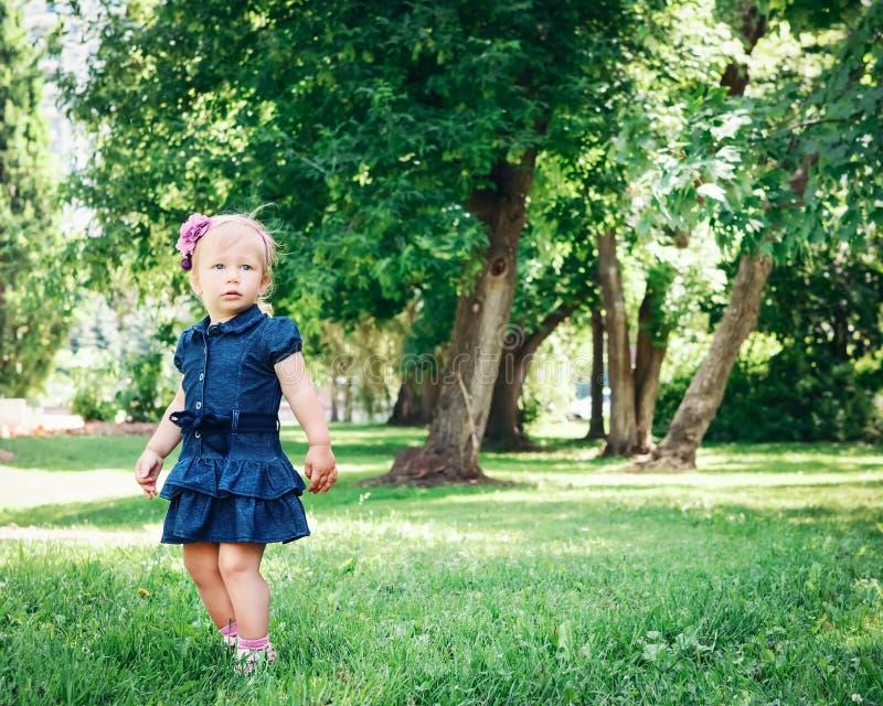 Kaukasisches Mädchenkind im blauen Kleid, das draußen im Feldwiesenpark steht lizenzfreies stockfoto