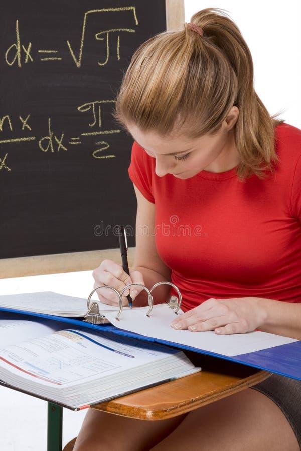 Kaukasisches Schulmädchen durch Schreibtisch Matheprüfung studierend stockbilder