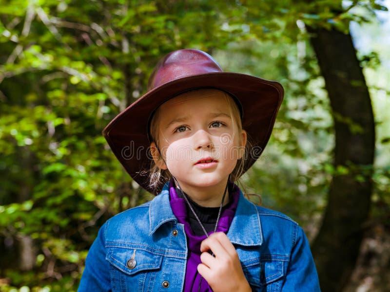 Kaukasisches Schulmädchen im Cowboyhut gehend in den Wald lizenzfreie stockfotografie