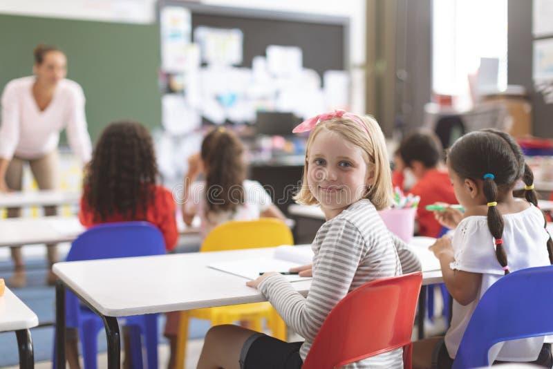 Kaukasisches Schulmädchen, welches die Kamera betrachtet und auf einem roten Stuhl sitzt stockbild