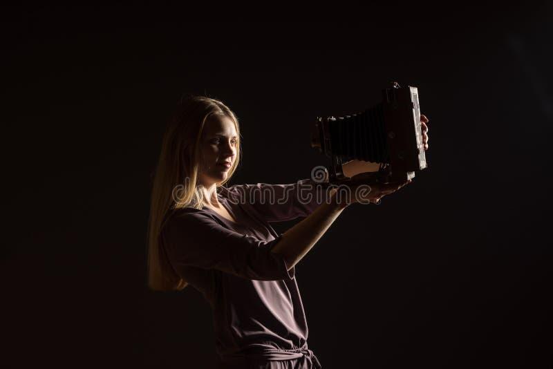 Kaukasisches weißes weibliches vorbildliches Porträt Schönes Mädchen, langes blondes Haar, das ein Foto mit der Kamera macht Frau lizenzfreie stockfotografie