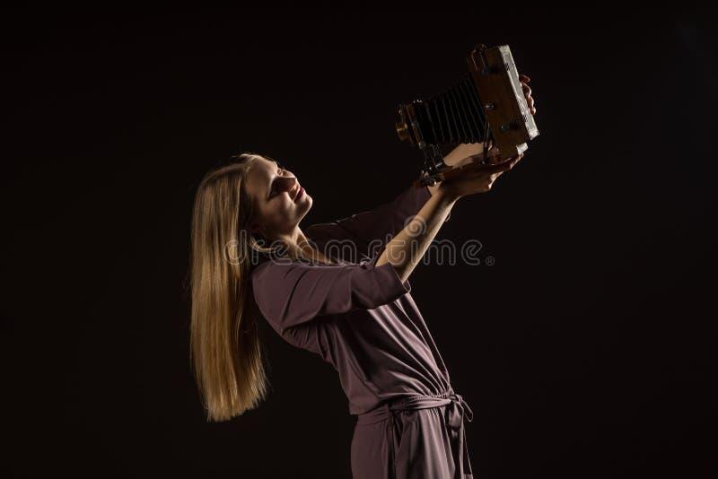 Kaukasisches weißes weibliches vorbildliches Porträt Schönes Mädchen, langes blondes Haar, das ein Foto mit der Kamera macht Frau lizenzfreies stockfoto