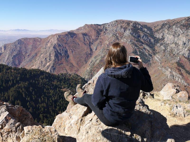 Kaukasisk hikerkvinna tar bilder överst i berget royaltyfria bilder