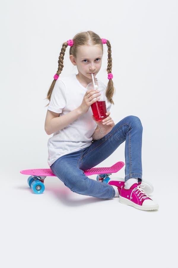 Kaukaska Blond dziewczyna z Długimi Pigtails Pozuje Z Różowym Pennyboard i Pije Czerwonego sok obrazy royalty free