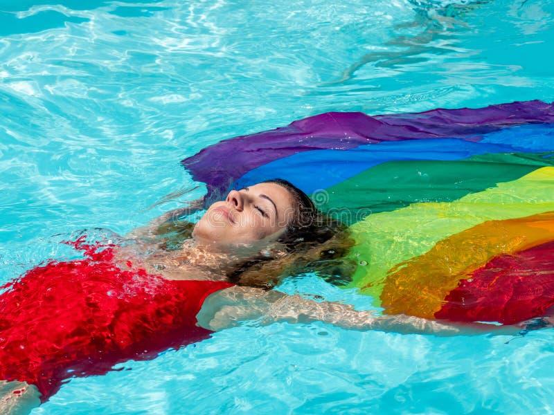 Kaukaska blondynki dziewczyna unosi się w basenie z flagą duma fotografia stock