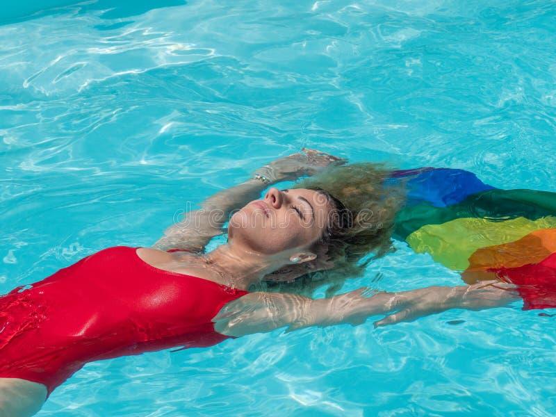 Kaukaska blondynki dziewczyna unosi się w basenie z flagą duma fotografia royalty free
