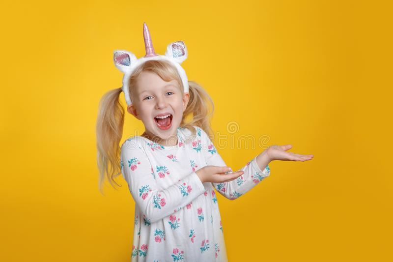Kaukaska blondynki dziewczyna w biel jednorożec kapitałki smokingowym jest ubranym rogu i ucho zdjęcie stock