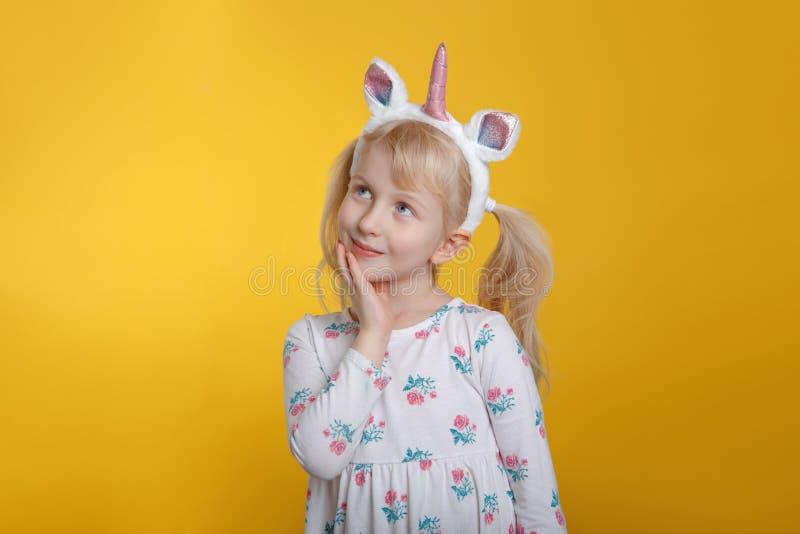 Kaukaska blondynki dziewczyna w biel jednorożec kapitałki smokingowym jest ubranym rogu i ucho obraz stock
