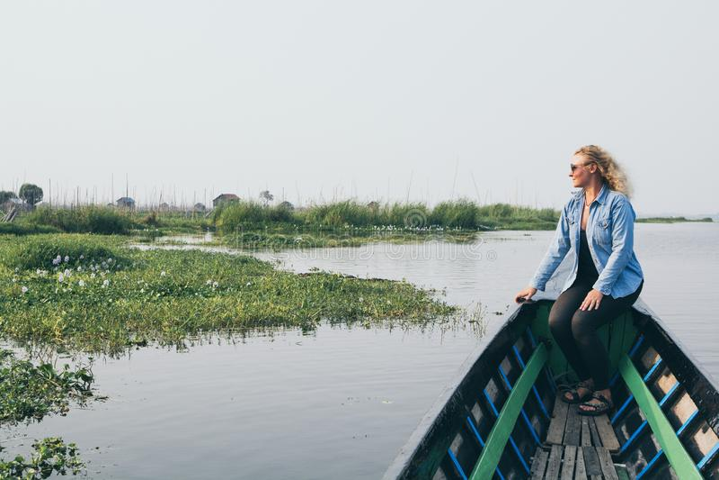 Kaukaska blondynki kobieta ma łódkowatą przejażdżkę na Inle jeziorze, Myanmar zdjęcie royalty free