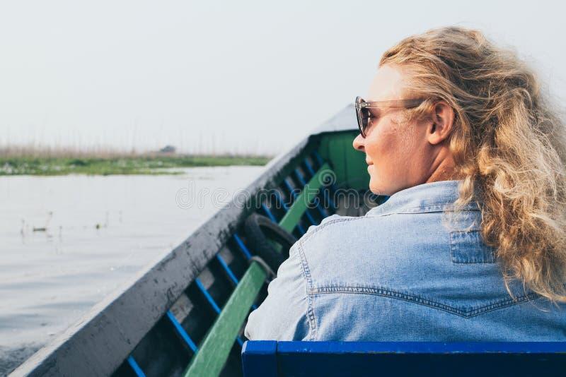 Kaukaska blondynki kobieta ma łódkowatą przejażdżkę na Inle jeziorze, Myanmar obrazy royalty free