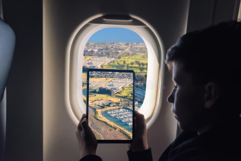 Kaukaska chłopiec używa pastylka komputer osobistego bierze obrazek przez samolotowych nadokiennych Redwood brzeg Twierdzi Morski zdjęcia stock