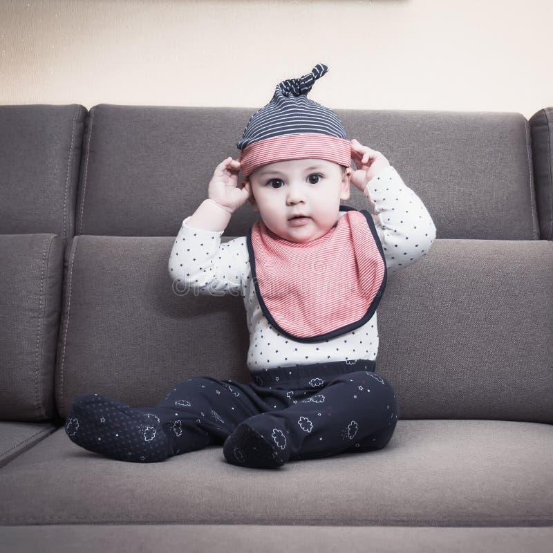 Kaukaska chłopiec weared śliniaczka obsiadanie na kanapie w domu zdjęcie stock