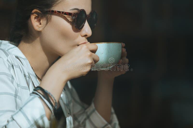 Kaukaska dziewczyna pije kawę w kawiarni, kawowej przerwy pojęcie zdjęcia stock