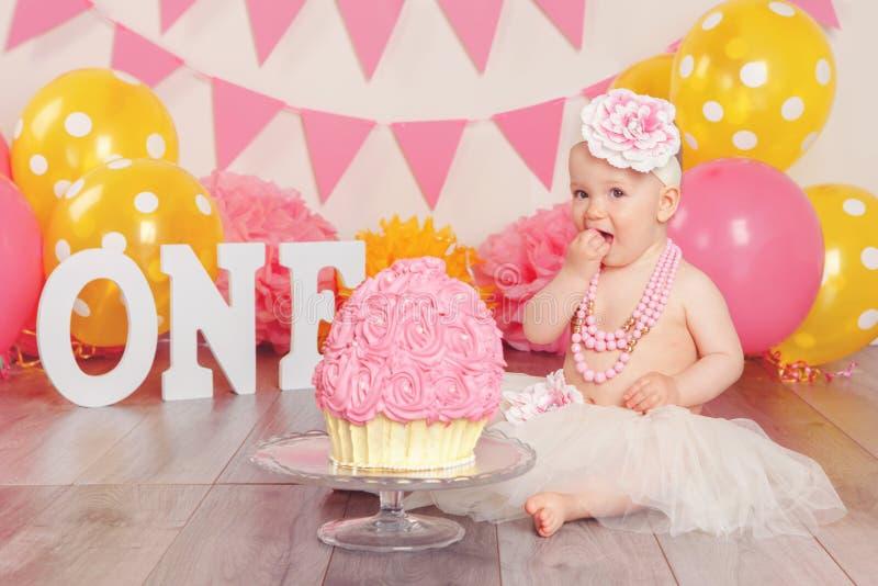 Kaukaska dziewczynka świętuje jej pierwszy urodziny w spódniczka baletnicy tiulu spódnicie Tortowy roztrzaskania pojęcie fotografia royalty free