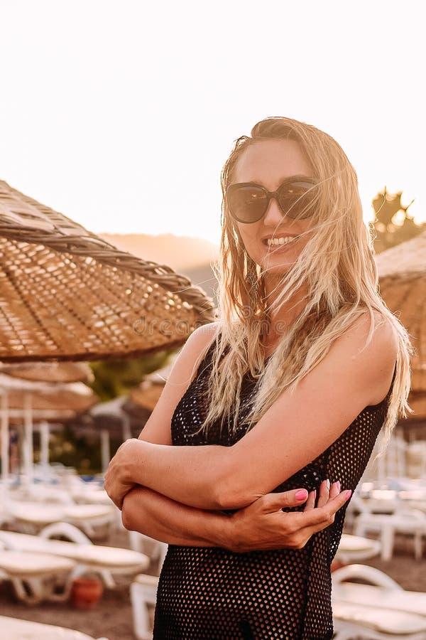 Kaukaska garbnikująca szczęśliwa stara kobieta z długie włosy na plaży w kontra światło słoneczne fotografia royalty free