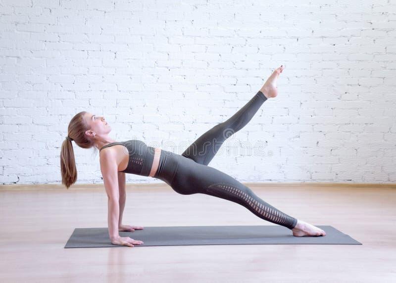Kaukaska kobieta robi odwrotnej desce na macie w pilates studiu, jeden noga w górę, boczny widok obrazy royalty free