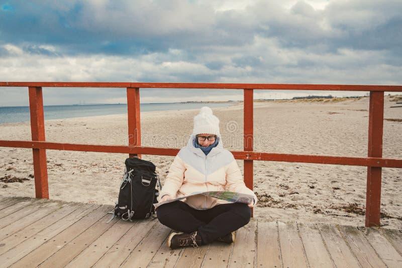 Kaukaska kobieta w kapeluszu i kurtce z plecakiem w zimie siedzi na drewnianym molu na plażowym pobliskim morzu północnym Dani zdjęcie stock