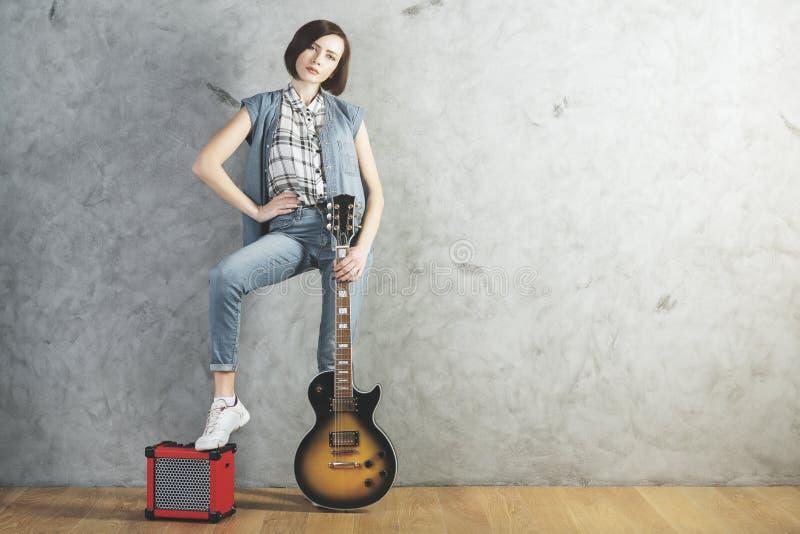 Kaukaska kobieta z gitarą w studiu fotografia stock