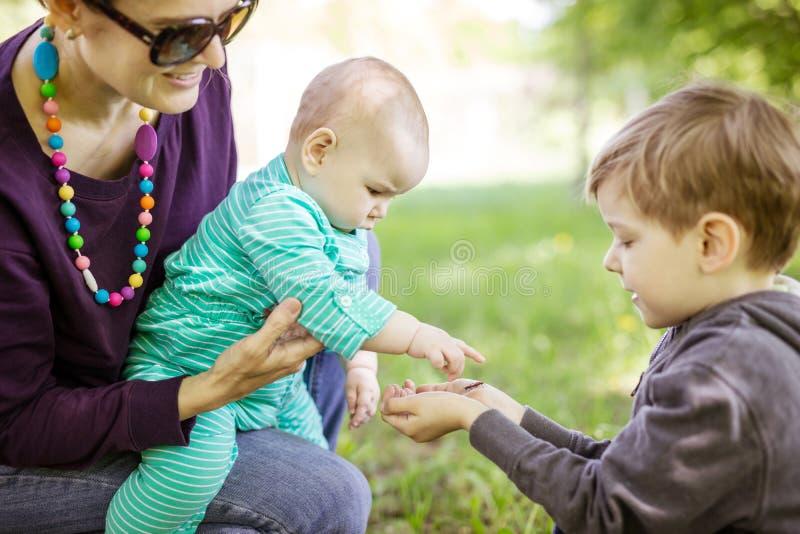 Kaukaska młodej kobiety mienia dziecka córka podczas gdy preschool pokazuje pluskwom na jego rękę zdjęcia stock