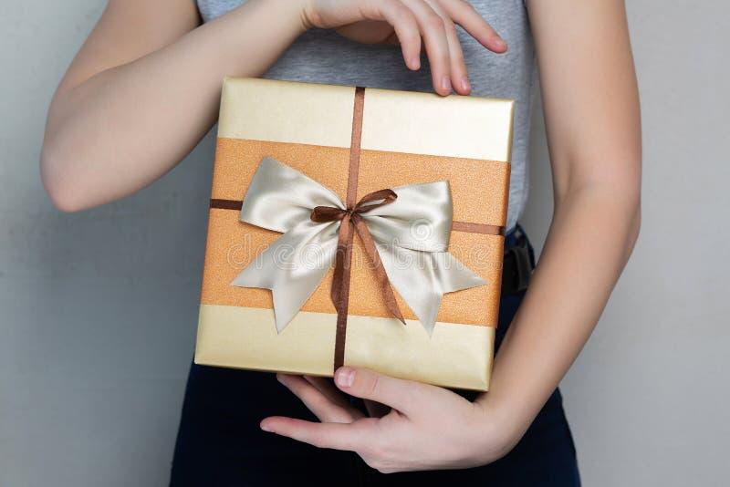 Kaukaska młoda dziewczyna jest ubranym t mienia prezenta koszulowego pudełko z łękiem obrazy stock