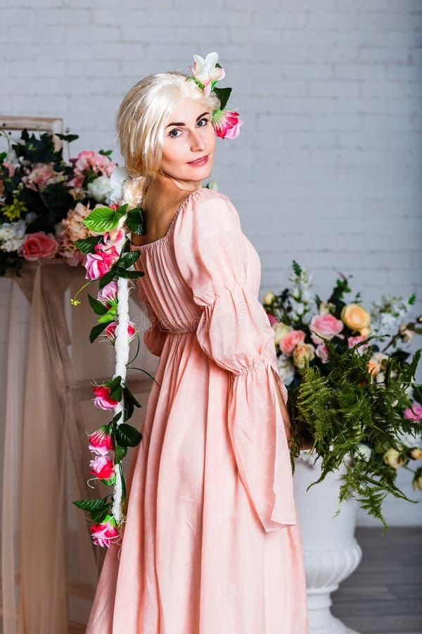 Kaukaska młoda kobieta w brzoskwini luźnej sukni i biała peruka na tła białych spojrzeniach przy kamerą zdjęcie stock