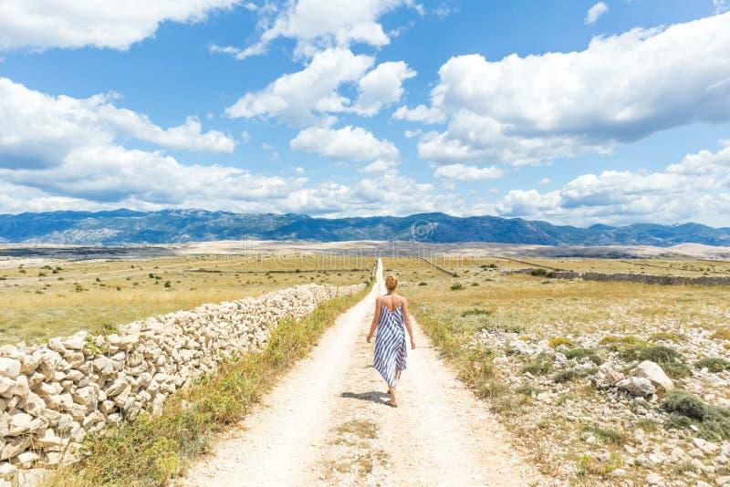 Kaukaska młoda kobieta w lato sukni mienia bukiecie lawenda kwitnie podczas gdy chodzący plenerowy przelotowy suchy skalistego zdjęcie royalty free