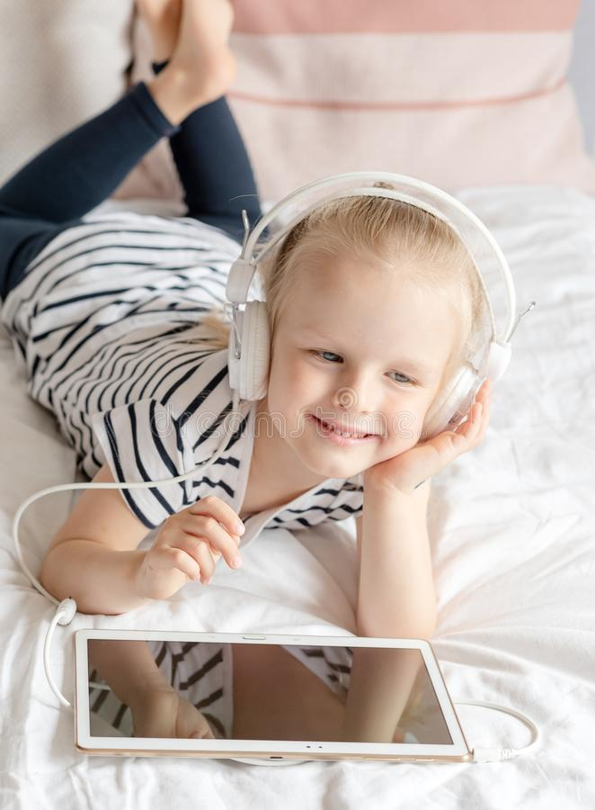 Kaukaska mała dziewczynka w hełmofonu dopatrywania pastylce w łóżku obrazy stock