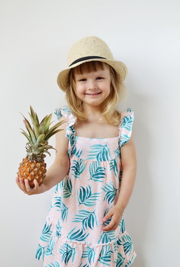Kaukaska mała dziewczynka w Kapeluszowego chwyta ananasa Soczystych Mini rękach zdjęcia stock