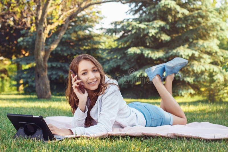 Kaukaska nastoletnia dziewczyna opowiada nad komórka telefonem komórkowym outside w parku obrazy stock