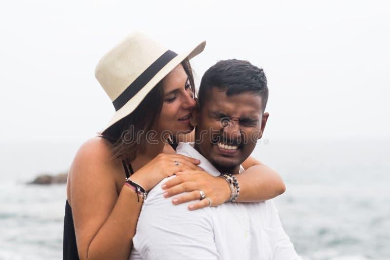 Kaukaska piękna kobieta ściska jej męża i gryźć jego ucho troszkę obrazy royalty free