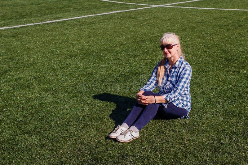 Kaukaska piękna kobieta siedzi na sztucznej trawie pięćdziesiąt rok w okularach przeciwsłonecznych obrazy royalty free
