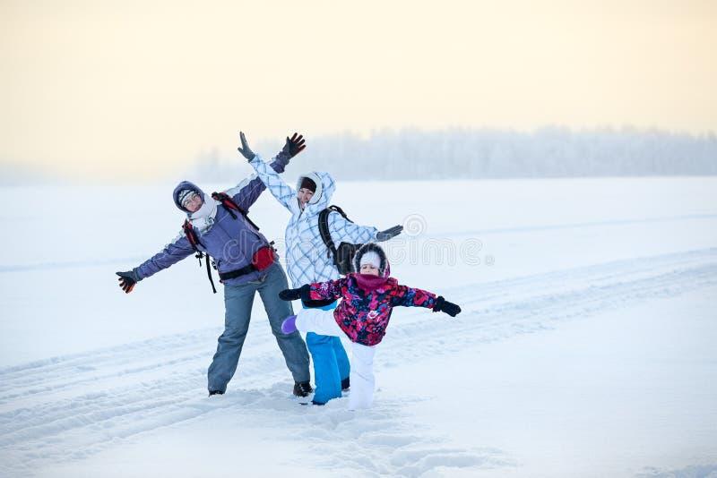 Kaukaska rodzina od trzy kobiet stoi z dźwiganie rękami na jeziorze, zimy wycieczkować obrazy royalty free