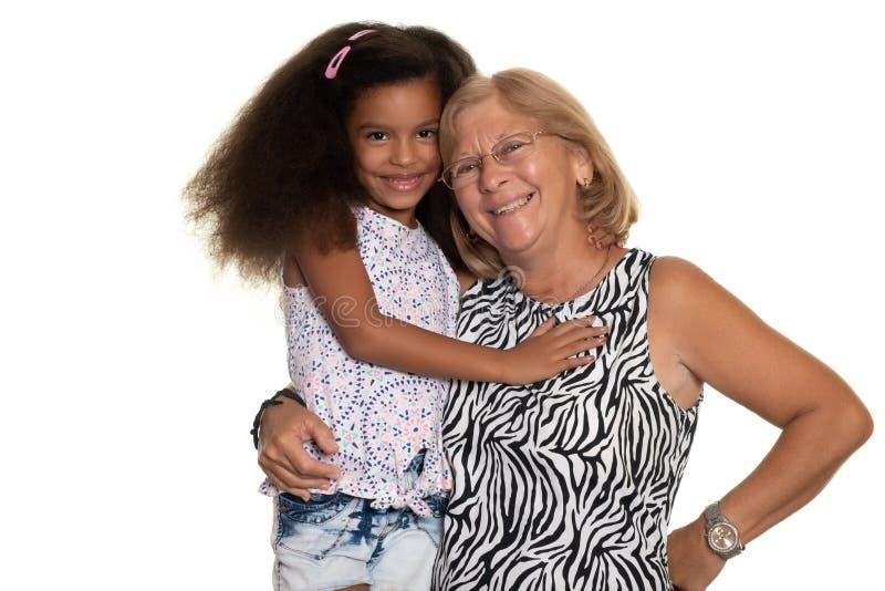 Kaukaska stara kobieta ściska jej amerykanin afrykańskiego pochodzenia wnuczki zdjęcia royalty free