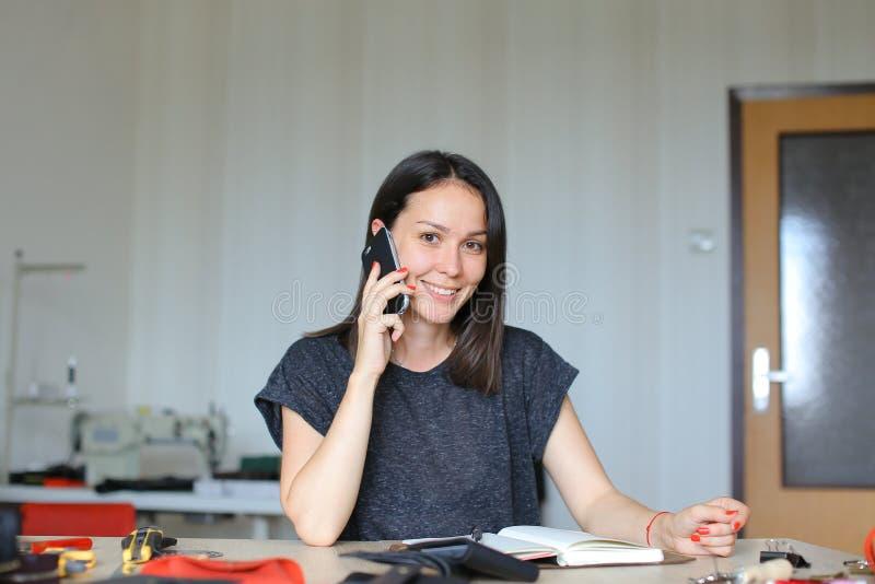 Kaukaski żeńskiej osoby obsiadanie przy rzemiennym atelier i robić handmade notatnikowi i portflom opowiada smartphone, zdjęcia stock